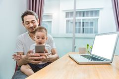 Padre e figlio asiatici che utilizza insieme Smart Phone nel contesto domestico Concetto della gente e di tecnologia Stili di vit fotografie stock