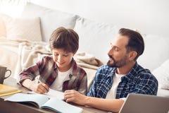 Padre e figlio a casa che si siedono alla tavola che fa insieme compito allegro immagine stock libera da diritti