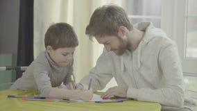 Padre e figlio che attingono carta che si siede insieme alla tavola relazione del Padre-bambino archivi video
