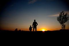 Padre e figlio che cercano futuro, concetto della siluetta fotografia stock