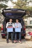 Padre e figlio che disimballano automobile per l'istituto universitario, recipienti di tenuta ed esaminanti macchina fotografica Fotografia Stock