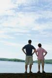 Padre e figlio che esaminano lago Fotografia Stock