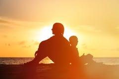 Padre e figlio che esaminano tramonto sulla spiaggia Fotografia Stock