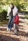 Padre e figlio che funzionano lungo il percorso del terreno boscoso Immagini Stock Libere da Diritti