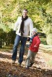 Padre e figlio che funzionano lungo il percorso di autunno Immagini Stock Libere da Diritti