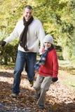 Padre e figlio che funzionano lungo il percorso di autunno Fotografia Stock