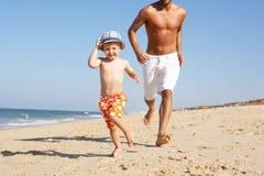Padre e figlio che funzionano lungo la spiaggia Fotografie Stock Libere da Diritti