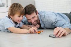 Padre e figlio che giocano con i giocattoli dell'automobile Immagine Stock Libera da Diritti