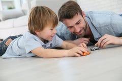 Padre e figlio che giocano con le automobili Immagine Stock