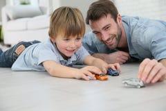 Padre e figlio che giocano con le automobili del giocattolo Fotografie Stock Libere da Diritti