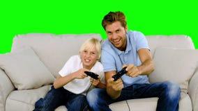 Padre e figlio che giocano i video giochi sul sofà sullo schermo verde stock footage