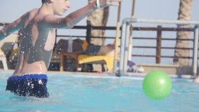 Padre e figlio che giocano pallanuoto nella piscina stock footage