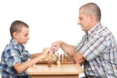 Padre e figlio che giocano scacchi Fotografie Stock