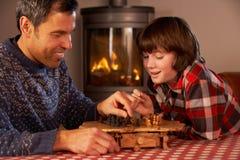 Padre e figlio che giocano scacchi dal fuoco di libro macchina Cosy Fotografia Stock