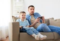 Padre e figlio che giocano video gioco a casa Fotografie Stock