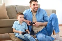 Padre e figlio che giocano video gioco a casa Immagine Stock Libera da Diritti