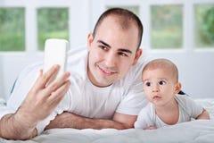 Padre e figlio che guardano al telefono e che prendono selfie Fotografia Stock