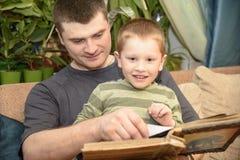 Padre e figlio che guardano un album di foto della famiglia, Ukreina fotografia stock