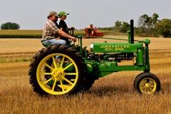 Padre e figlio che guidano un trattore per tutti gli usi di John Deere Immagini Stock Libere da Diritti