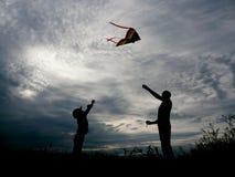 Padre e figlio che lanciano un aquilone al tramonto Immagini Stock Libere da Diritti