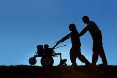 Padre e figlio che lavorano la terra con un attrezzo Immagine Stock Libera da Diritti