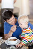 Padre e figlio che mangiano una prima colazione Fotografia Stock Libera da Diritti