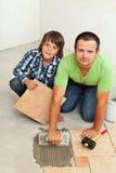 Padre e figlio che montano insieme le piastrelle per pavimento ceramiche Immagini Stock