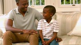 Padre e figlio che parlano sul sofà stock footage