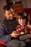 Padre e figlio che per mezzo del calcolatore del ridurre in pani Fotografia Stock