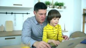 Padre e figlio che per mezzo del computer portatile Padre bello che esamina computer con il figlio molto sveglio a casa Giorno de video d archivio