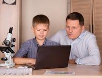 Padre e figlio che per mezzo del computer portatile Padre che aiuta suo figlio che fa scuola Immagini Stock Libere da Diritti