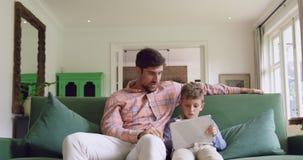 Padre e figlio che per mezzo della compressa digitale sul sof? a casa 4k archivi video