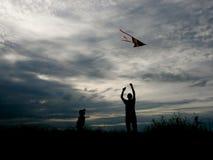 Padre e figlio che pilotano un aquilone al tramonto Immagini Stock Libere da Diritti