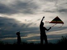Padre e figlio che pilotano un aquilone sui precedenti di bello tramonto Fotografia Stock Libera da Diritti