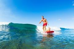 Padre e figlio che praticano il surfing insieme, Wave di guida Fotografie Stock Libere da Diritti