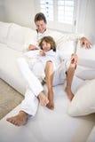 Padre e figlio che si distendono insieme sul sofà bianco fotografia stock