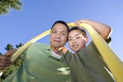 Padre e figlio che si levano in piedi sotto Palo - orizzontale Fotografie Stock