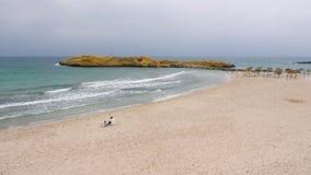 Padre e figlio che si siedono insieme sulla spiaggia sola vuota vicino al mare archivi video