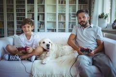 Padre e figlio che si siedono sul sofà con il cane di animale domestico e che giocano i video giochi immagine stock libera da diritti