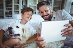 Padre e figlio che si siedono sul sofà con il cane di animale domestico e che per mezzo della compressa digitale fotografia stock libera da diritti
