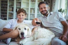Padre e figlio che si siedono sul sofà con il cane di animale domestico e la televisione di sorveglianza immagini stock