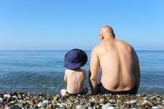 Padre e figlio che si siedono sulla spiaggia immagini stock libere da diritti