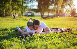 Padre e figlio che si trovano sull'erba nel fine settimana, famiglia, vacanza Immagine Stock Libera da Diritti