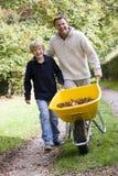 Padre e figlio che spingono carriola Fotografie Stock Libere da Diritti