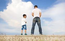 Padre e figlio che stanno insieme su una piattaforma e su una pipi di pietra immagine stock libera da diritti