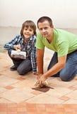 Padre e figlio che verificano il colore materiale unito sulle piastrelle di ceramica Fotografia Stock