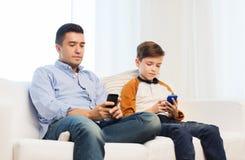 Padre e figlio con gli smartphones a casa Fotografia Stock