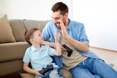 Padre e figlio con i gamepads che fanno livello cinque Immagine Stock