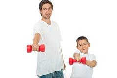 Padre e figlio con il barbell Fotografie Stock