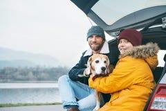 Padre e figlio con il cane del cane da lepre che colloca insieme nel tronco di automobile e fotografia stock libera da diritti